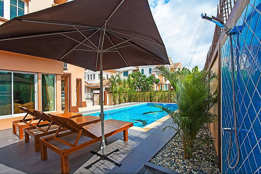 Pool deck with sun beds and umbrella at Jomtien Summertime Villa B Pattaya