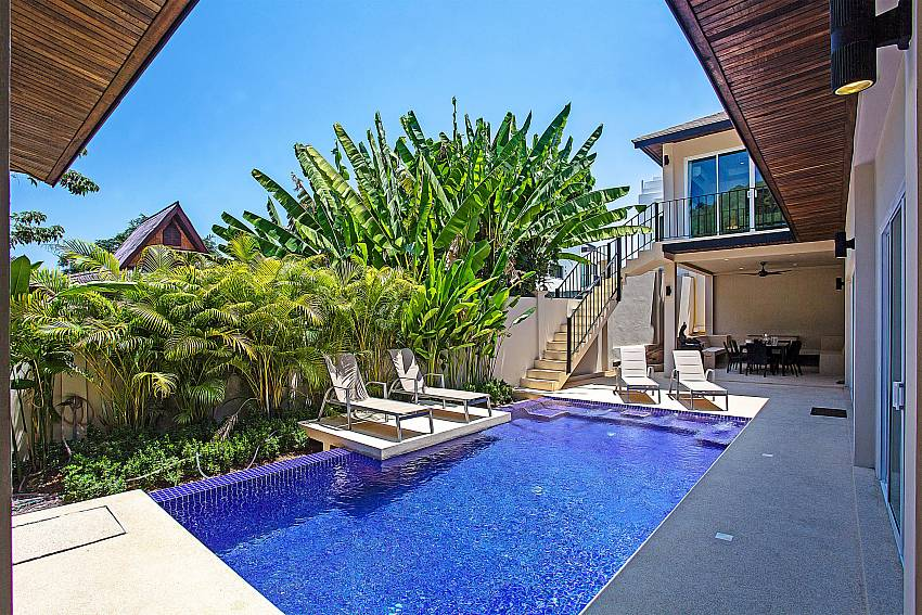 Swimming pool with tree and sun bed Of Rawayana Pool Villa