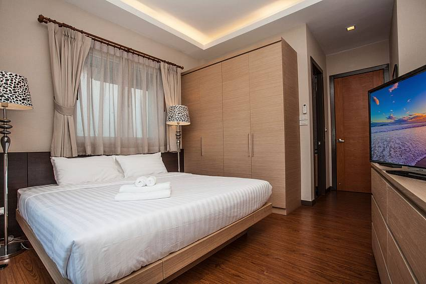 King-size bed with TV and wardrobe at Jomtien LAmore Villa Pattaya