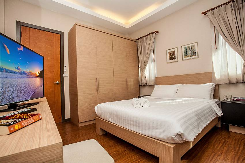 Guest bedroom with king size bed and TV at Jomtien LAmore Villa Pattaya
